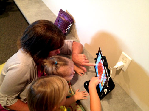 From top to bottom: Carly Ahlbrand, the Sengs' niece, Piper Seng and Susan Ahlbrand playing on a tablet in the waiting area.