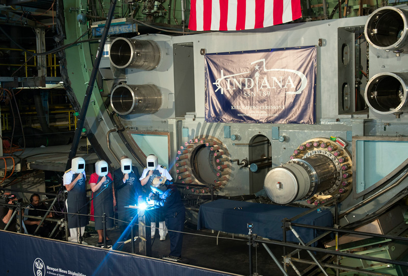 A welder carves the initials of ship's sponsor Diane Donald on a metal plate during the keel laying ceremony for the future Virginia-class attack submarine Indiana (SSN 789). (U.S. Navy photo courtesy of Huntington Ingalls Industries by Ricky Thompson/Released)