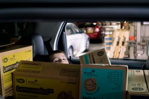 Tax Jacob, 3, of Ferdinand, peaked over cases of cookies his babysitter Tara Vaught picked up at OFS Brands Plant 8 Tuesday.
